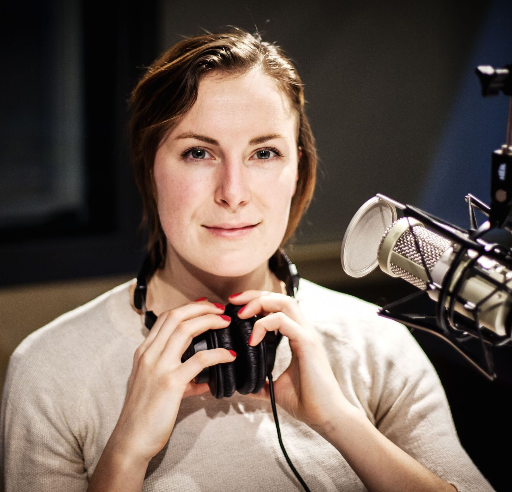 A headshot image of a young woman with brunette hair, wearing a white t-shirt with headphones around her neck. Her hands are clutching the headphones and her fingernails are painted pink.